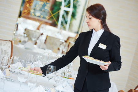 people eating restaurant: Restaurant catering services. Waitress with food dish serving banquet table