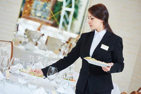 meseros: Servicios de catering del restaurante. Camarera con el plato de comida que sirve mesa del banquete