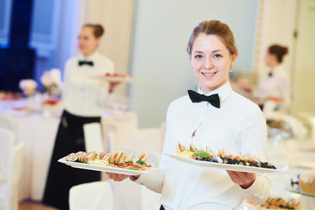 servings: waitress occupation. Young woman with food on dishes servicing in restaurant during catering the event