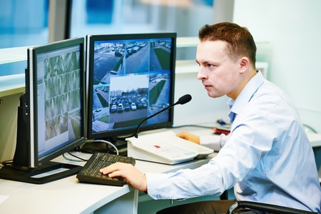 chief: security guard officer watching video monitoring surveillance security system Stock Photo