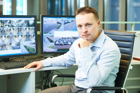 video surveillance: security guard officer watching video monitoring surveillance security system Stock Photo