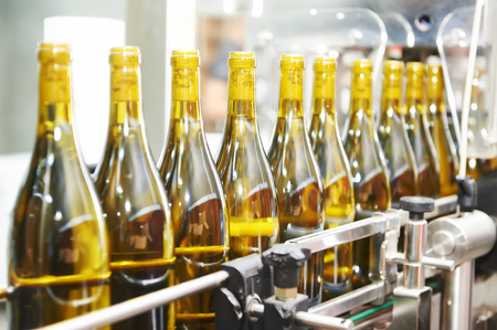 botella: Botellas con el vino en el embotellado y sellado l�nea de producci�n transportadora en la f�brica moderna bodega. DOF bajo. Foto de archivo