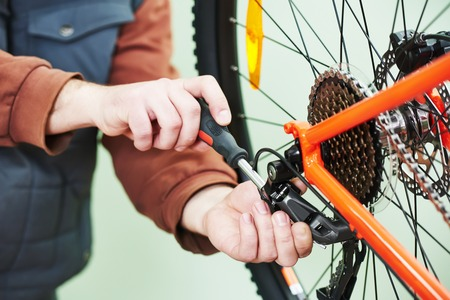 Fahrrad-Service: Mechaniker serviceman Reparateur Installation Montage oder Einstellung Fahrradgang auf dem Rad in der Werkstatt Standard-Bild