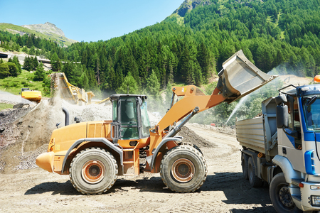 heavy wheel side loader excavator machine loading sand into dump truck at mountain quarry