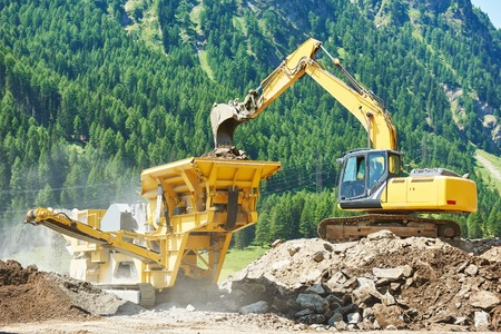shredder machine: excavator loads the ground in the stone crusher machine during earthmoving works outdoors at mountains construction site