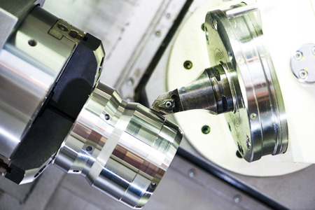 tool chuck: modern metal working machine with cutter tool during metal detail turning at factory Stock Photo