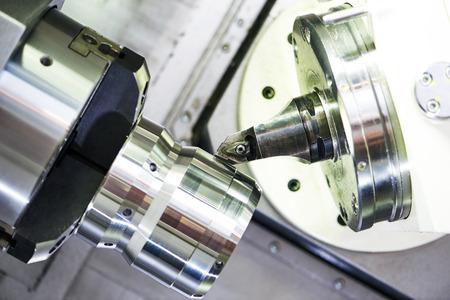 machine tool: modern metal working machine with cutter tool during metal detail turning at factory Stock Photo