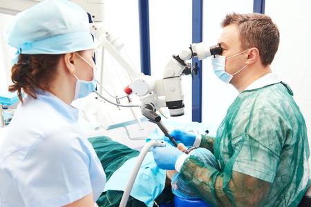 odontologa: Odontología. médico dentista hombre y asistente femenina trabaja con el microscopio en el consultorio dental Foto de archivo