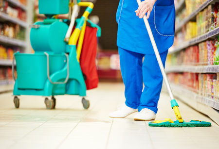 Female cleaner worker in uniform  with mop cleaning the floor of supermarket shop store Reklamní fotografie