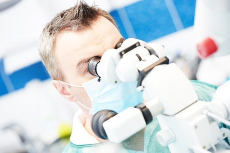 stomatology: Dentistry. Dentist male doctor using microscope for operation at dentistry office