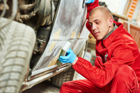 service station: auto mechanic worker sanding body car at automobile repair and renew service station shop by sandpaper
