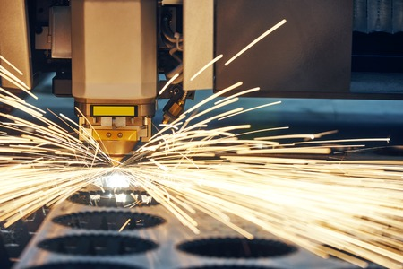 manufacture: metal working. Laser cutting technology of flat sheet metal steel material processing with sparks. Authentic shooting in challenging conditions.