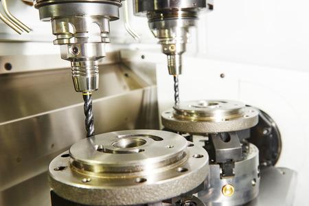 industrie: Metall-Industrie. Fräsen Werkzeugmaschine mit zwei Mühlen in Futter vorbereitet, Metalldetail in der industriellen Fertigung Fabrik verarbeiten