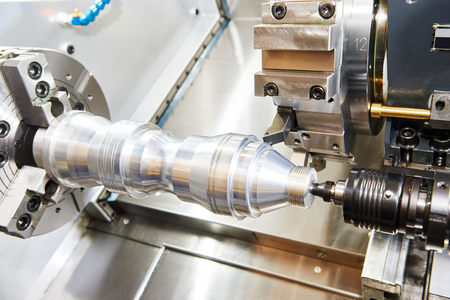 hard alloy: metalworking  industry: cutting steel metal shaft processing on lathe machine in workshop. Selective focus on tool Stock Photo