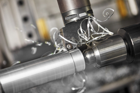 metalworking  industry: cutting steel metal shaft processing on lathe machine in workshop. Selective focus on tool Stock Photo