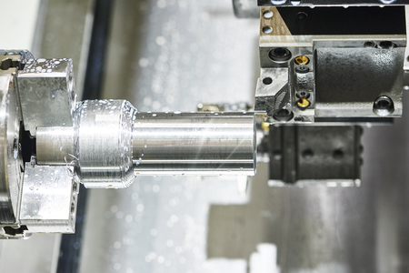 shaft: metalworking  industry: cutting steel metal shaft processing on lathe machine in workshop. Selective focus on tool Stock Photo