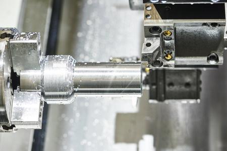 metalworking: metalworking  industry: cutting steel metal shaft processing on lathe machine in workshop. Selective focus on tool Stock Photo