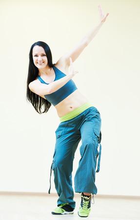 zumba: hembra instructor de baile firness haciendo ejercicios de baile en el gimnasio