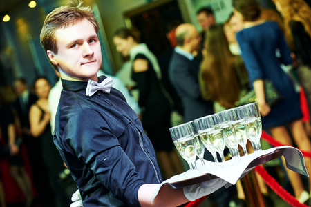 catering or celebration concept. male waiter holding a tray with glasses of vine at party, Authentic shot in mixed light conditions