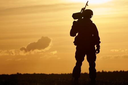 pistolas: militar. silueta de soldado en uniforme con la ametralladora o fusil de asalto en el verano por la noche la puesta de sol