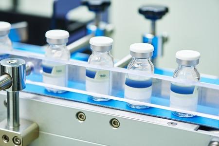 medicamento: industria farmacéutica. Línea de producción transportador de la máquina con las botellas de vidrio ampollas en la fábrica