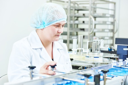 pharmaceutical plant: pharmaceutical factory woman worker operating production line at pharmacy industry manufacture factory Stock Photo