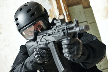 contractor: military industry. Portrait of special forces or anti-terrorist police soldier, private contractor armed with assault rifle ready to attack during clean-up operation, mission Stock Photo