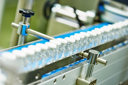 plastic industry: pharmaceutical industry. Production line machine conveyor with glass bottles ampoules at factory Stock Photo