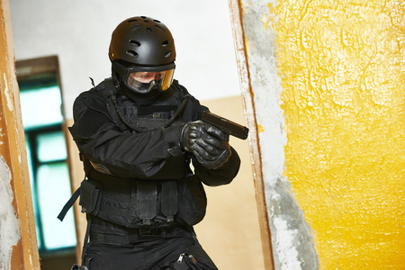 contractor: Military industry. Special forces or anti-terrorist police soldier, private contractor armed with pistol ready to attack during clean-up operation, mission