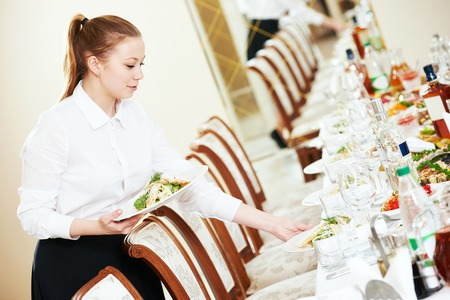 holiday catering: Restaurant catering services. Waitress with salad dish serving banquet table Stock Photo