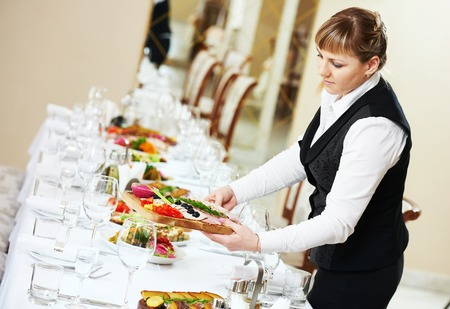banquet table: Restaurant catering services. female waitress serving banquet table Stock Photo