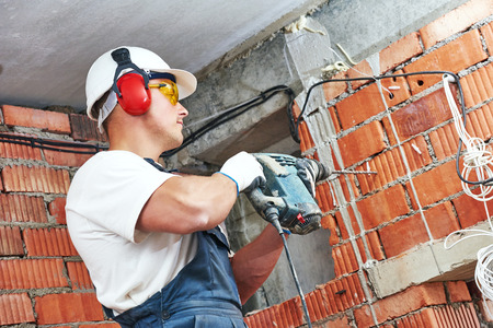 drilling: Builder worker with pneumatic hammer drill perforator equipment making hole in wall at construction site Stock Photo
