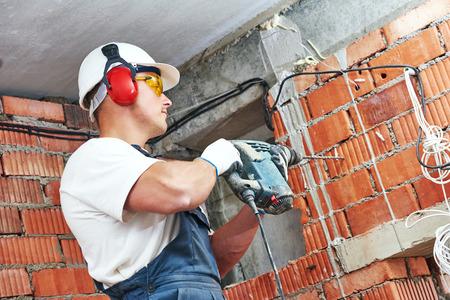 trabajadores: Trabajador del constructor con el agujero que hace el equipo perforador taladro martillo neum�tico en la pared en el sitio de construcci�n