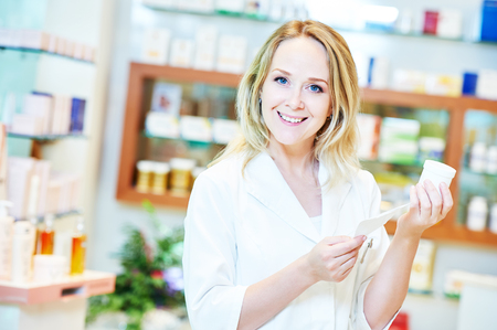 druggist: portrait of cheerful smiling female pharmacist chemist woman in pharmacy drugstore