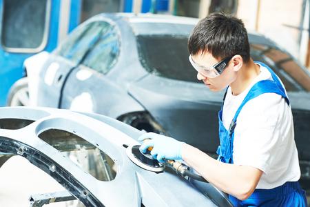 grinder machine: auto mechanic worker sanding bumper car at automobile repair and renew service station shop by grinder machine