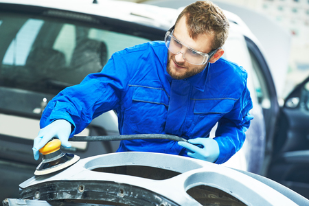 buffing: auto mechanic worker  polishing bumper car at automobile repair and renew service station  by power polisher machine Stock Photo