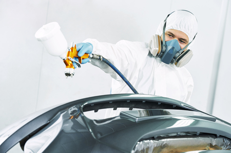 protective workwear: automobile repairman painter in protective workwear and respirator painting car body bumper in paint chamber Stock Photo