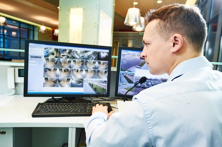 security room: security guard officer watching video monitoring surveillance security system Stock Photo