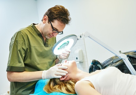 Male doctor cosmetologist examining young woman skin with loupe before the cosmetology procedure Stock Photo