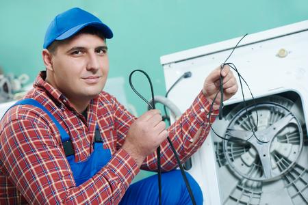replacing: Washing machine repair. Mechanic repairer replacing rubber drive belt