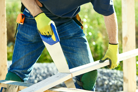 trussing: Closeup construction roofer carpenter worker sawing wood board with hand saw outdoors Stock Photo