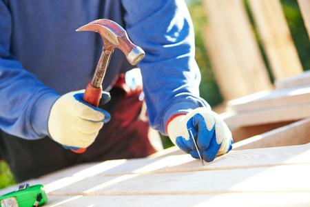carpintero: Un primer plano de las manos de los trabajadores de sexo masculino carpintero que martilla el clavo en el tablero al aire libre