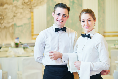 hotel staff: waiter and waitress occupation. Young man and woman at catering service in restaurant during event