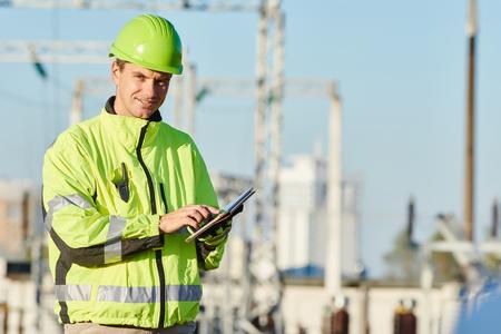 albañil: constructor ingeniero con la computadora portátil en sitio de construcción cerca de la planta de energía Foto de archivo