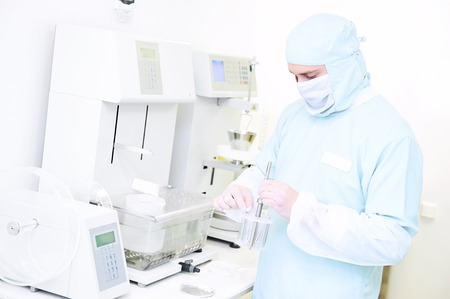 abrasion: Pharmaceutical scientific male researcher in protective uniform working with friability, abrasion and disintegration tester at pharmacy industry manufacture factory laboratory