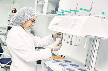 drug: Pharmaceutical scientific  female researcher in protective uniform working with dissolution tester at pharmacy industry manufacture factory laboratory Stock Photo