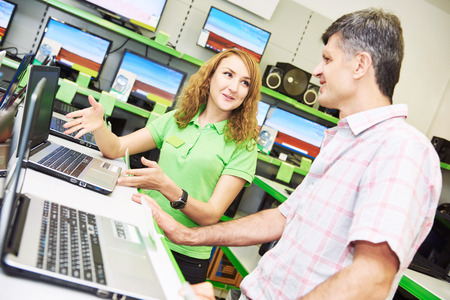 purchaser: Shopping concept. Happy seller assistant woman help purchaser choosing notebook computer in electronics supermarket shop