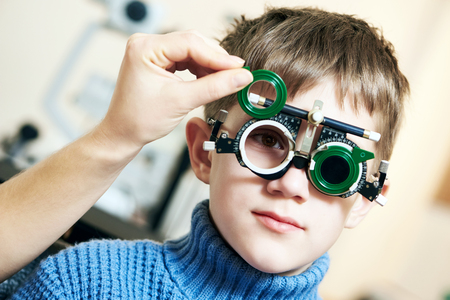 optometry: Optometry concept. Young boy with phoropter during sight testing or eye examinations in ophthalmological clinic Stock Photo