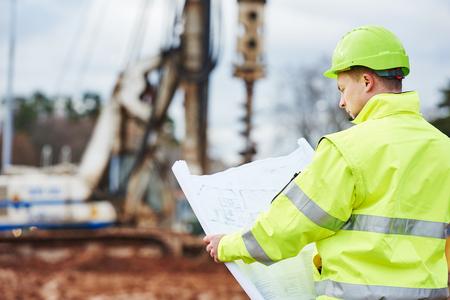 dibujo tecnico: constructor ingeniero con Modelo del plan en el sitio de construcción