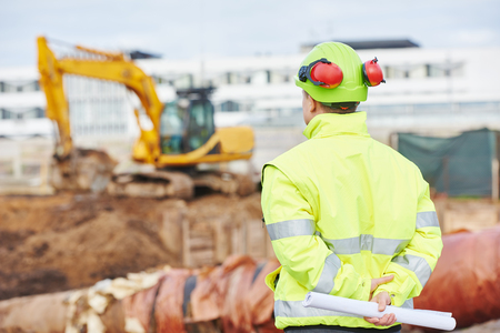 albañil: constructor ingeniero con Modelo del plan en el sitio de construcción